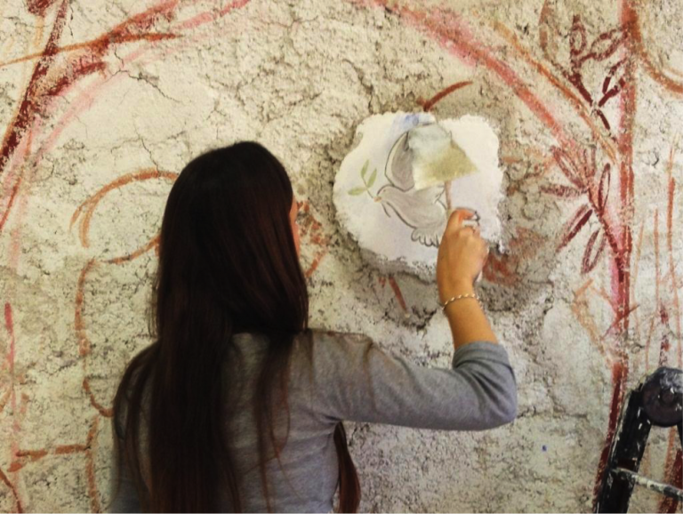 A JCU student tries her hand at Michelangelo's famous fresco technique