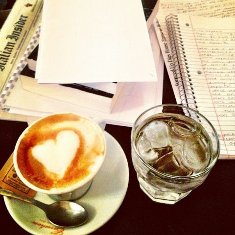 A JCU student enjoys heart-topped espresso while studying in a Roman cafe