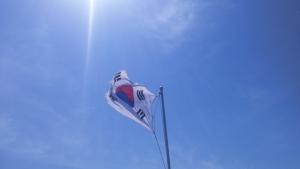 대국기, the Korean flag, against the sky over the mountains.