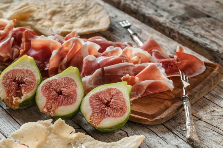 Fresh figs with ham on a white plate, Carciofi alla romana, Best Seasonal Dishes to Try While Studying abroad in Rome, rome open markets, Italian food culture, study abroad in Rome