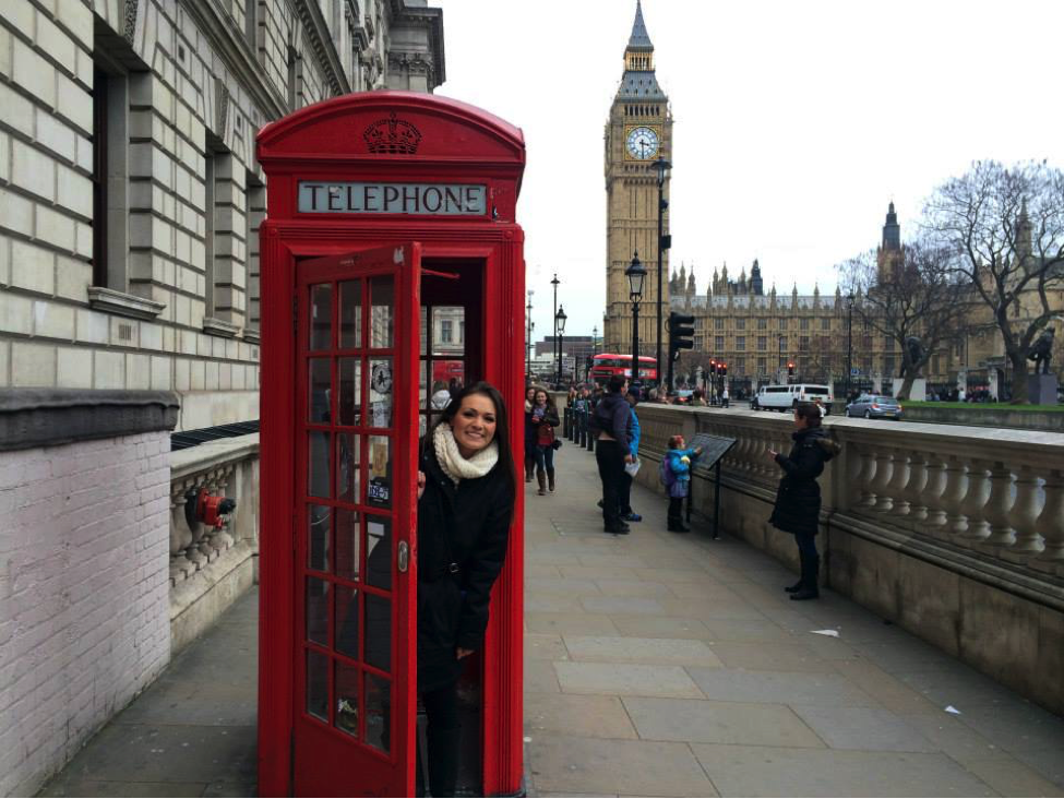 "A John Cabot University student poses in a famous ""red phone booth"" with Big Ben in the background"