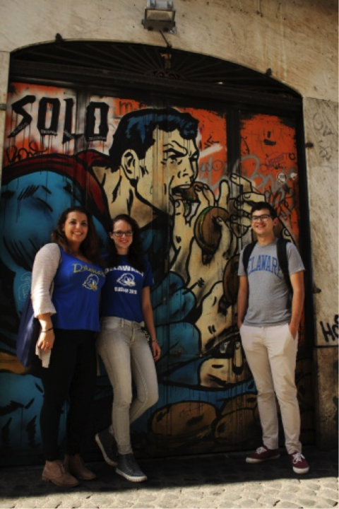 JCU students pose in front of some of Rome's colorful graffiti.