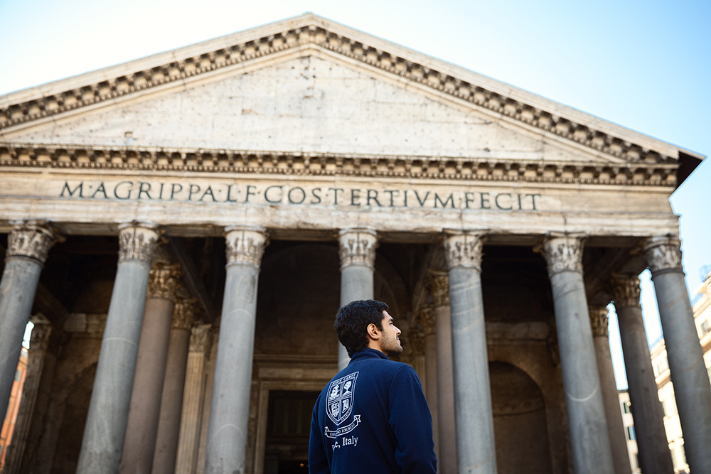Student in John Cabot logo in front of the Pantheon in Rome, Italy