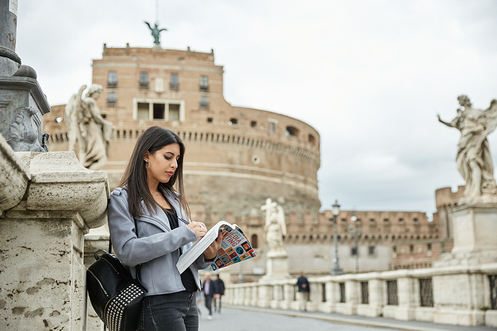 Girl (brown hair on the side view) with book in hand on a bridge in front of Castel Sant'Angelo in Rome, Italy